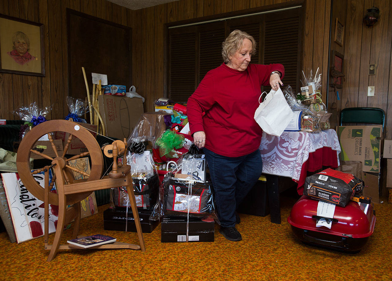 Volunteer Anne Grimm chooses an item to label in Darlene Strotz's rec room on Tuesday. (Andy Bronson / The Herald)