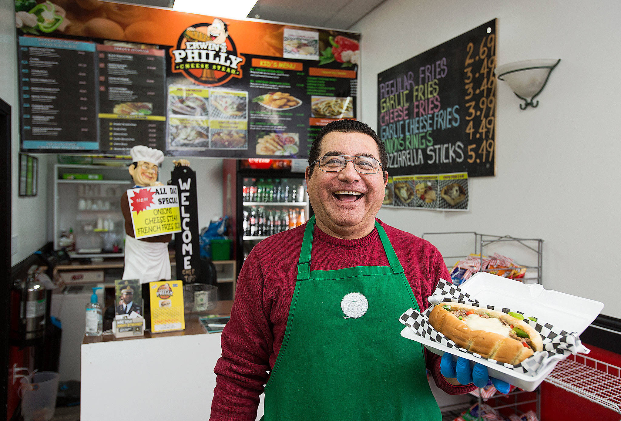 Erwin Sanchez, owner of Erwin's Philly Cheese Steak, holds up one of the selections from the menu at his Everett restaurant. (Andy Bronson / The Herald)