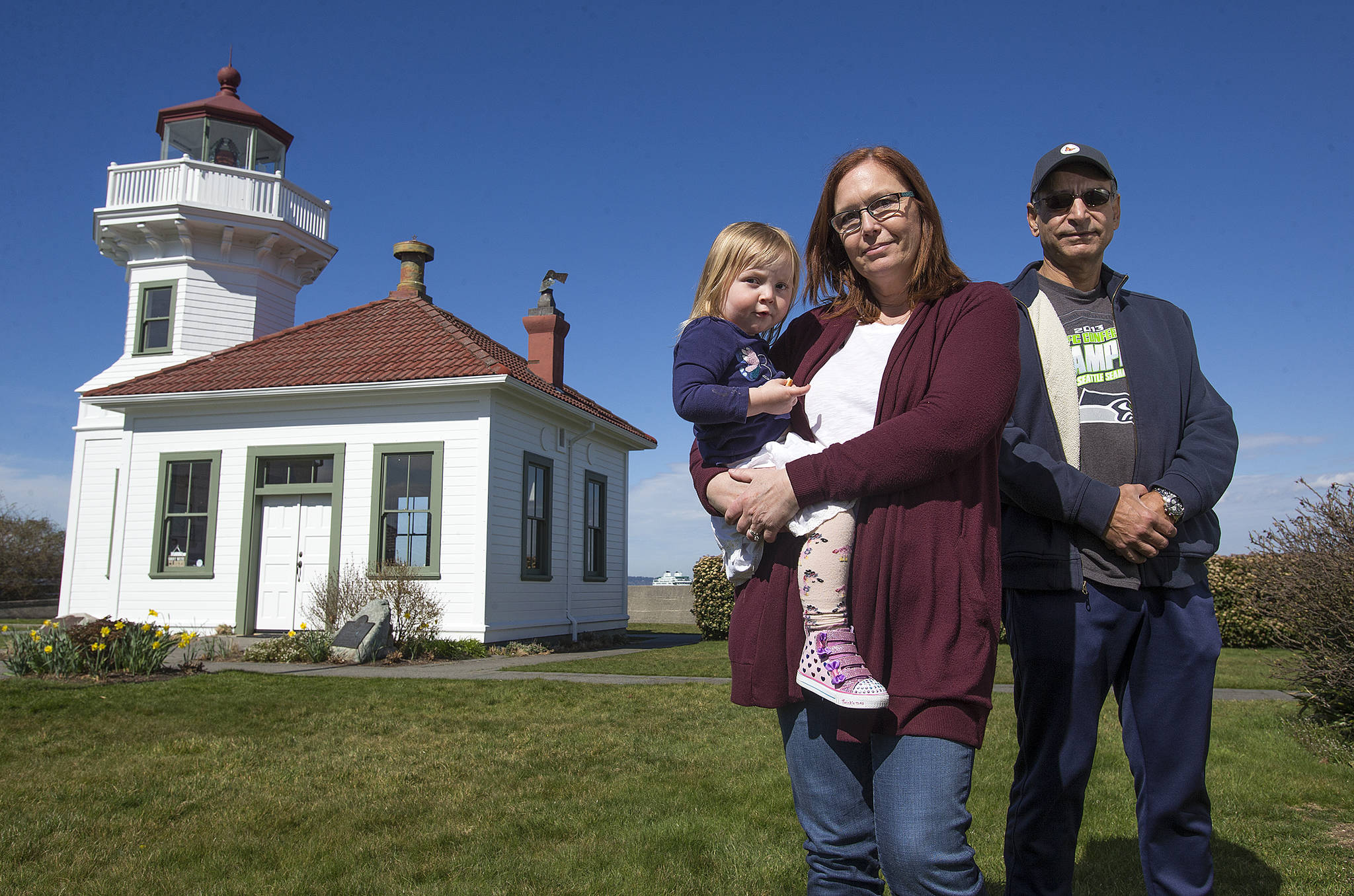 """Andy Bronson / The Herald                                  Mukilteo Lighthouse Festival Association President Julie Martin, holding her granddaughter, Ariah Martin, 2, and Bashar Elali, vice president. Martin says the festival could use help. """"We still have a large chunk of last year's festival to pay off, so we're working on coming up with some fundraisers."""""""