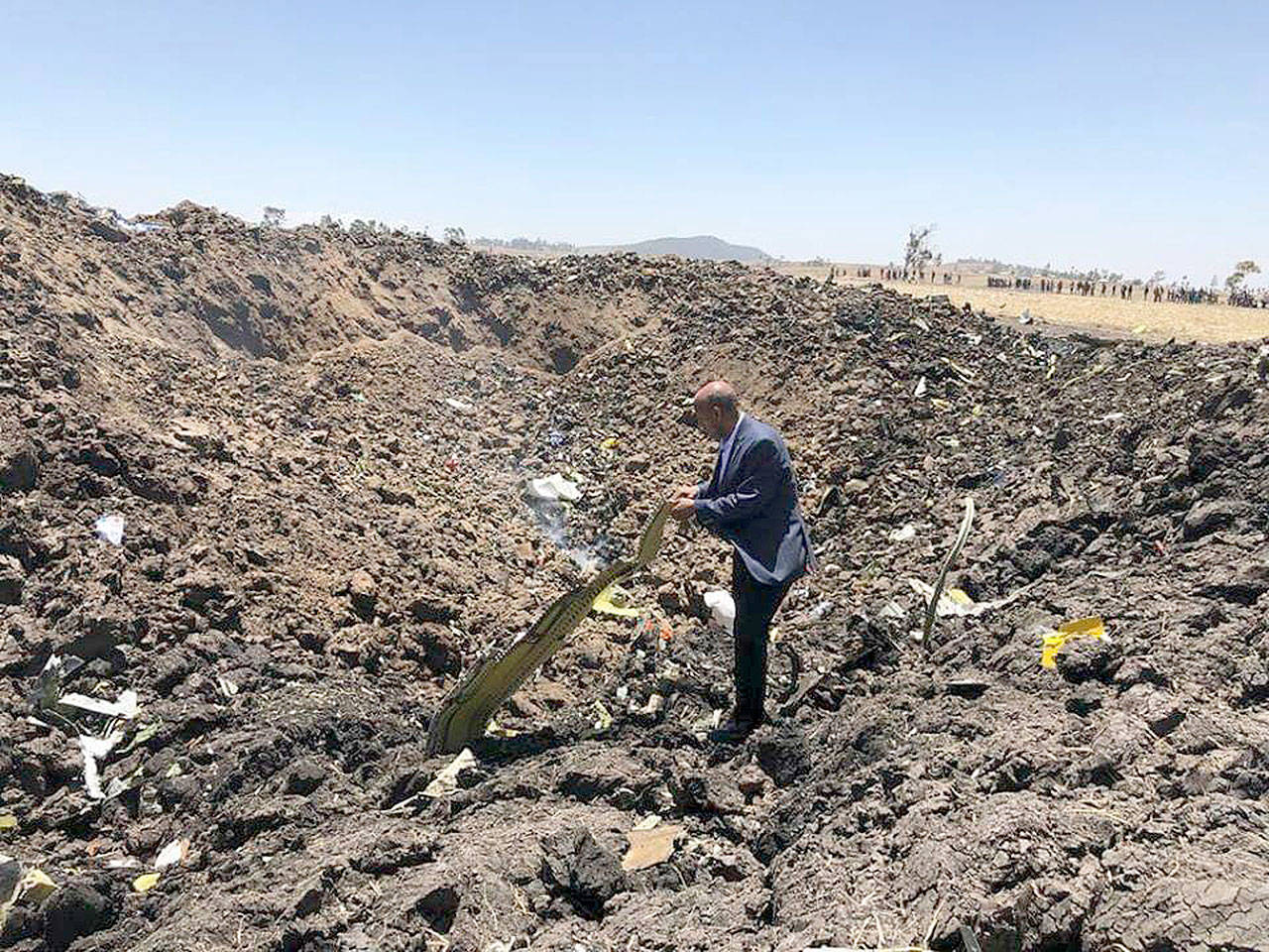 In this photo taken from the Ethiopian Airlines Facebook page, the CEO of Ethiopian Airlines, Tewolde Gebremariam, looks at the wreckage of the plane that crashed shortly after takeoff from Addis Ababa, Ethiopia, Sunday March 10. All 157 people thought to be on board died, the airline and state broadcaster said, as anxious families rushed to airports in Addis Ababa and the destination, Nairobi. (Facebook via AP)