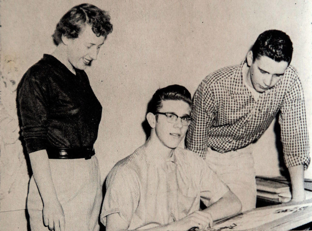Artist Chuck Close (center) was among Ruth May Scougate's students who worked on the yearbook at Everett High School. A photo from the 1957 Nesika shows Close and classmates Barbara Wick and Chuck Thorpe looking at his work. (Dan Bates / The Herald)