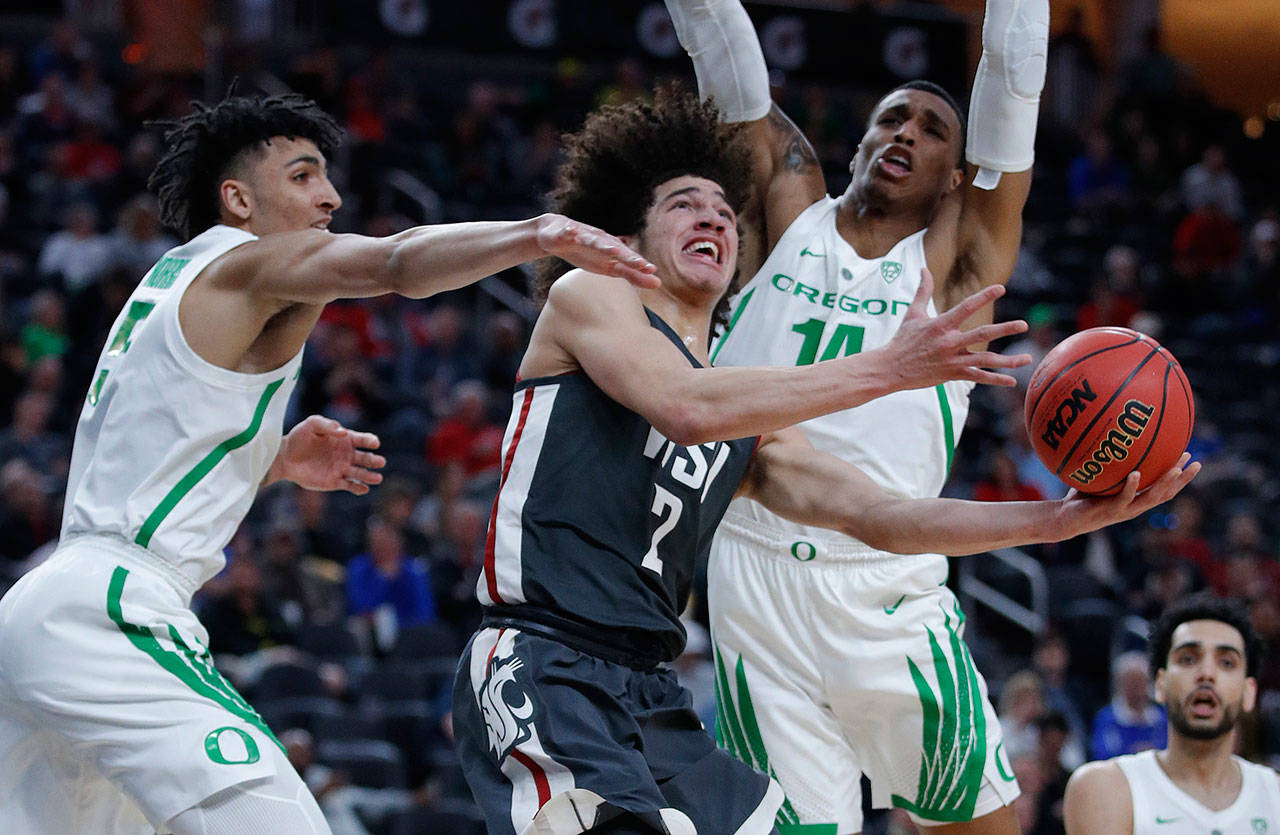 Washington State's CJ Elleby (center) shoots between Oregon's Miles Norris (left) and Kenny Wooten during a first-round Pac-12 tournament game on March 13, 2019, in Las Vegas. (AP Photo/John Locher)
