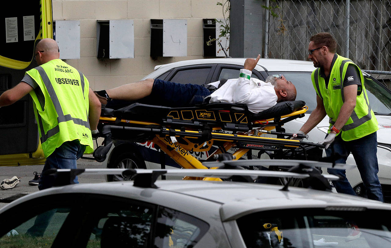Ambulance staff take a man from outside a mosque in central Christchurch, New Zealand, on Friday. A witness says many people have been killed in a mass shooting at a mosque in the New Zealand city of Christchurch. (AP Photo/Mark Baker)