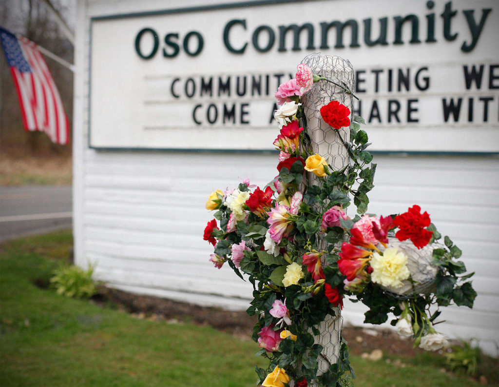 A cross is decorated with flowers in dedication of mudslide victims at the Oso Community Chapel on March 26, 2014. (Sofia Jaramillo / The Herald)