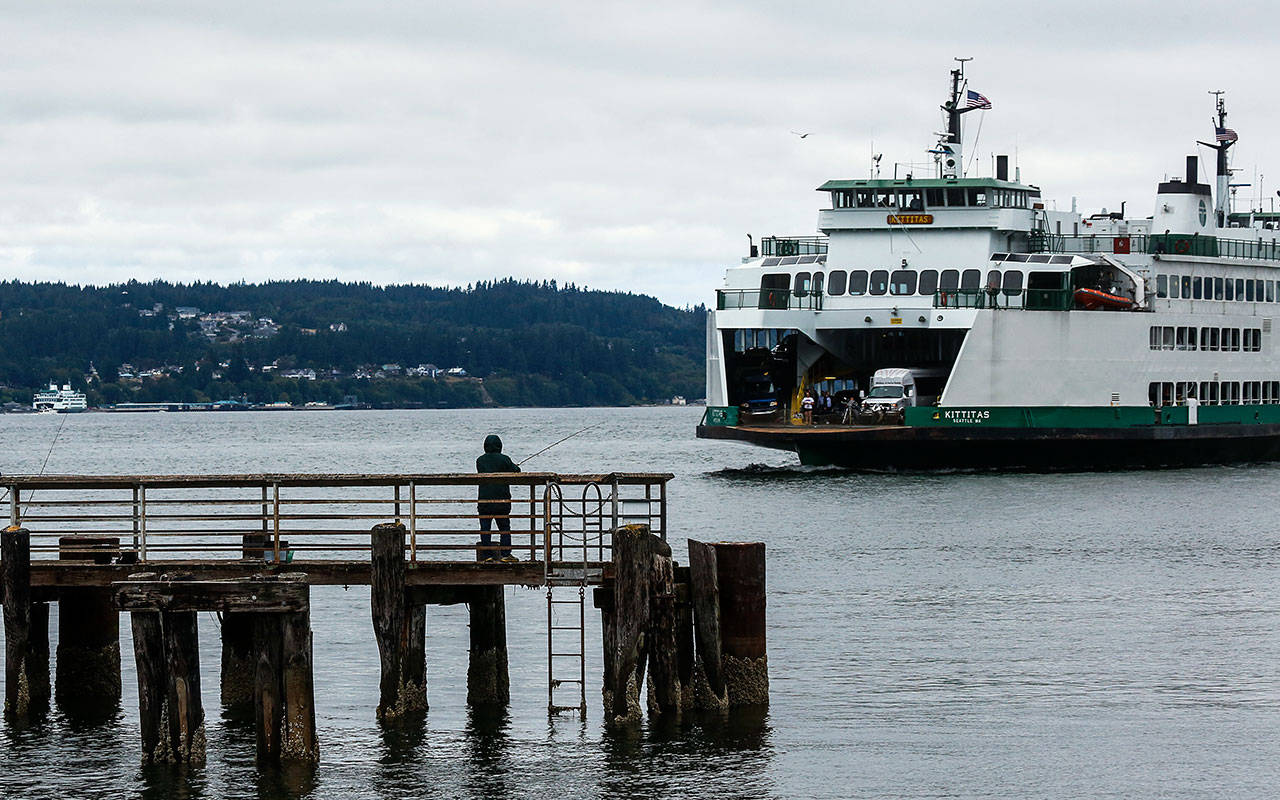 A fisherman waits for a catch in July 2018 at the fishing pier adjacent to the Mukilteo Ferry Terminal. Catching a Washington State Ferries vessel may cost more if a budget proposal by House Democrats is approved. (Dan Bates / The Herald)