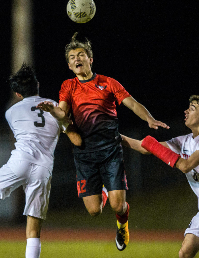 Stanwood's Shintaro Wilcox (center) jumps for a header. (Olivia Vanni / The Herald)