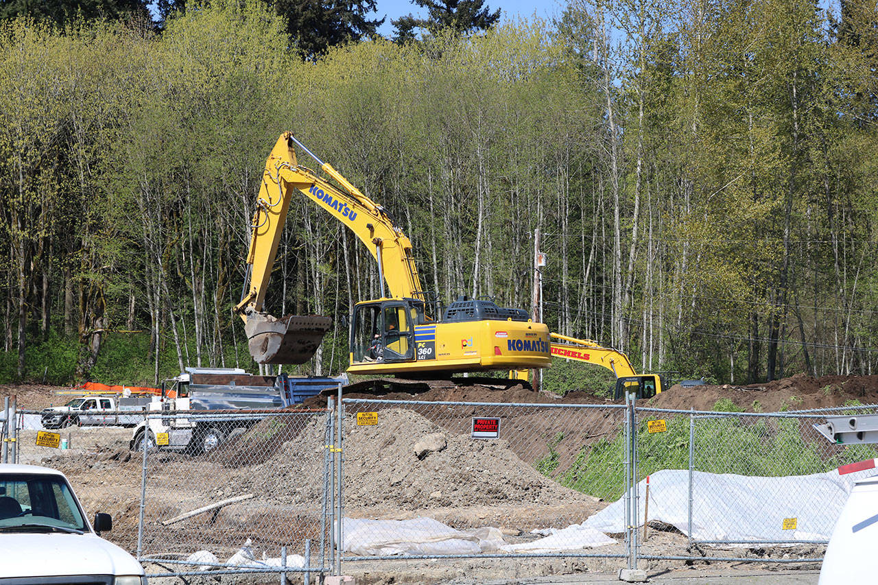 Country Village sat on 13 acres in north Bothell, but around 6 acres were sold to developers who are building more than 90 townhomes on the land. An excavator crew is pictured at work here on a recent afternoon. (Aaron Kunkler / Bothell-Kenmore Reporter)