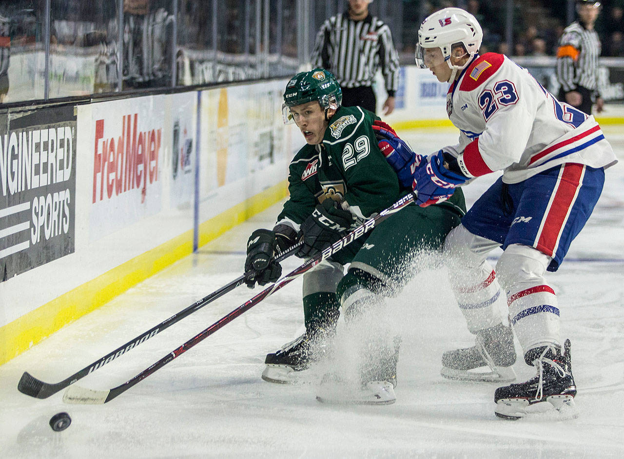 The Silvertips' Wyatte Wylie (left) fights for the puck during the a against the Chiefs on Nov. 18, 2018, in Everett. (Olivia Vanni / The Herald)