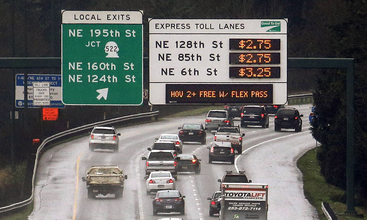 This 2016 photo shows signs with the rates for using the express toll lanes for traffic headed southbound on I-405 in Bothell. (AP Photo/Elaine Thompson, file)