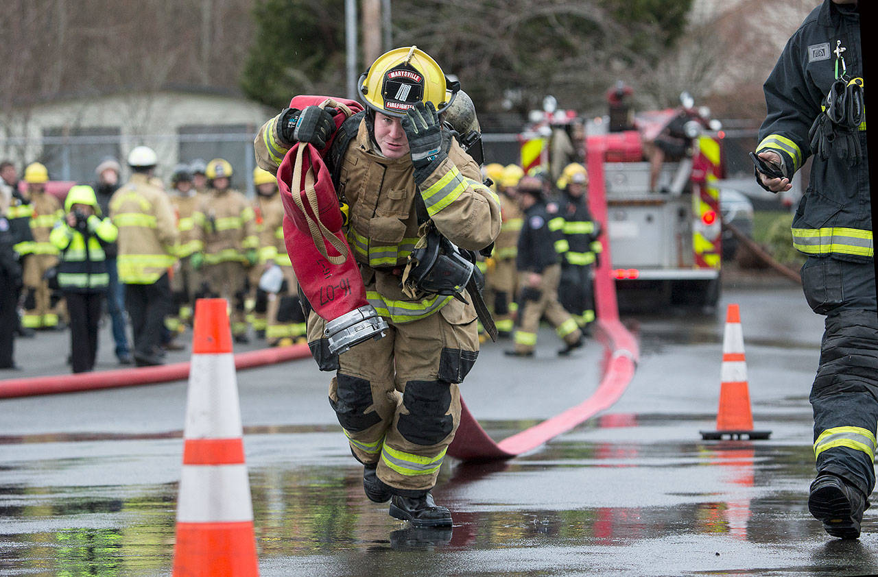 Marysville fire recruit Brian Donaldson holds onto his helmet as he drags a 5-inch line 200 feet in Snohomish County's first fire training academy, through an obstacle course at the South Snohomish Fire & Rescue training ground in March, 2018 in Everett. (Andy Bronson / The Herald)