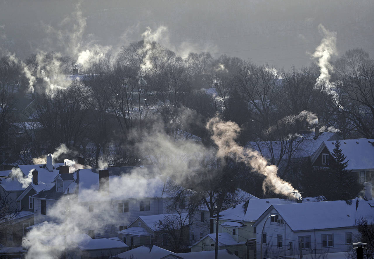Smoke rises from the chimneys of homes in St. Paul, Minnestoa. Americans burned a record amount of energy in 2018, with a 10% jump in consumption from booming natural gas helping to lead the way, the U.S. Energy Information Administration says. (Brian Peterson/Star Tribune via AP, File)