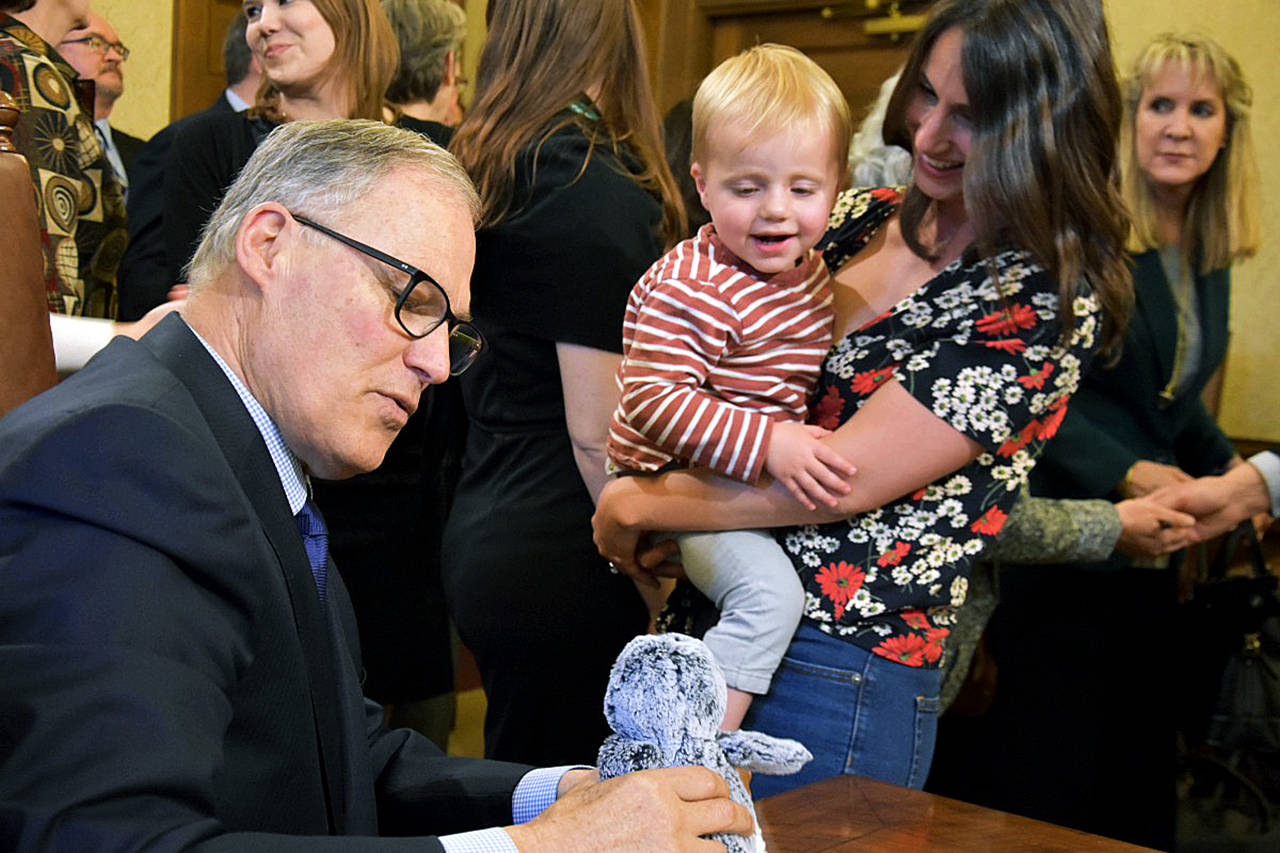 Nikki Dziedzic and her two-year-old son Jude look on as Gov. Jay Inslee props up Jude's stuffed penguin while signing HB 1870 on April 17. (Office of the Governor photo)