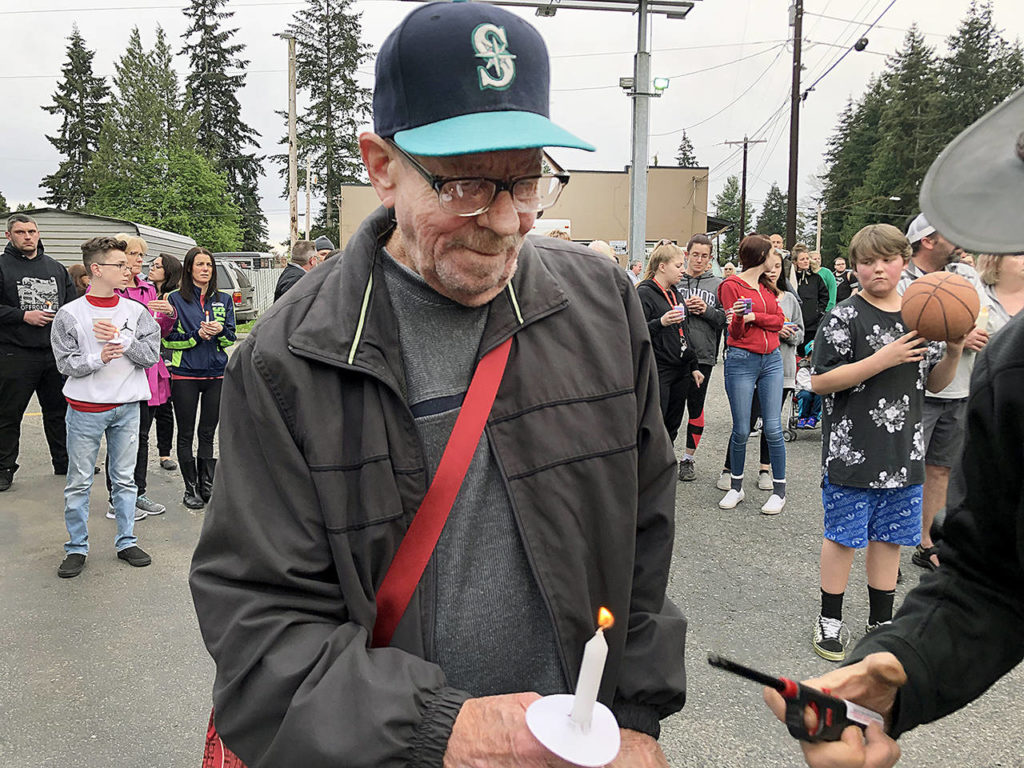 Dozens of people gathered Thursday night to remember Jae An, 58, a mini mark clerk killed in a robbery on Broadway in Everett. (Caleb Hutton / The Herald)