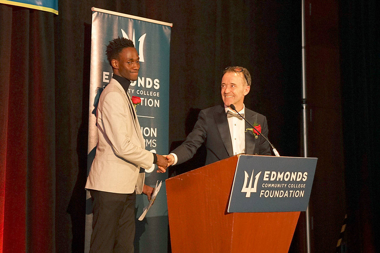 Kevin Joyce (right), emcee for the Edmonds Community College Foundation's awards gala, presents student Mustapha Samateh the Student Spotlight. Samateh shared his story of overcoming adversity when he came to the U.S. as a student seeking political asylum from The Gambia. (Edmonds Community College)