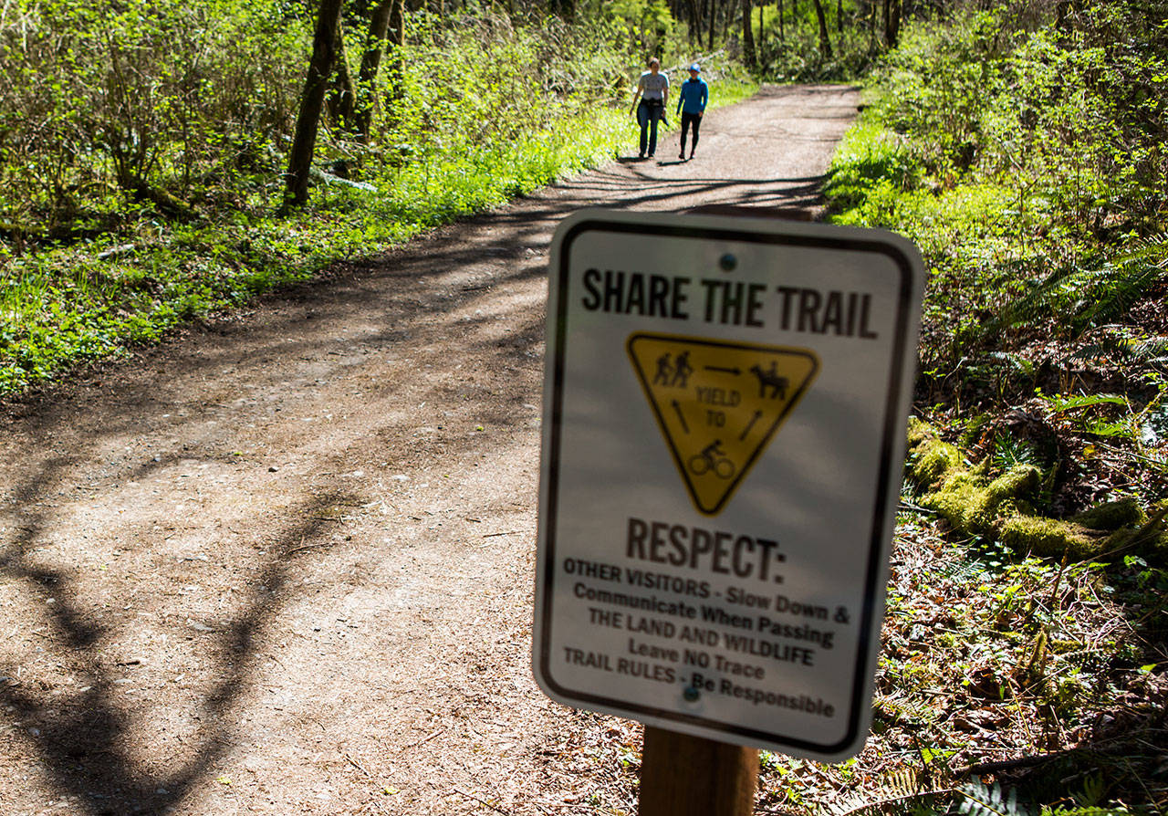 A sign reminding park goers to 'share the trail' along the Main Trail at Lord Hill Regional Park on April 4 in Snohomish. (Olivia Vanni / The Herald)
