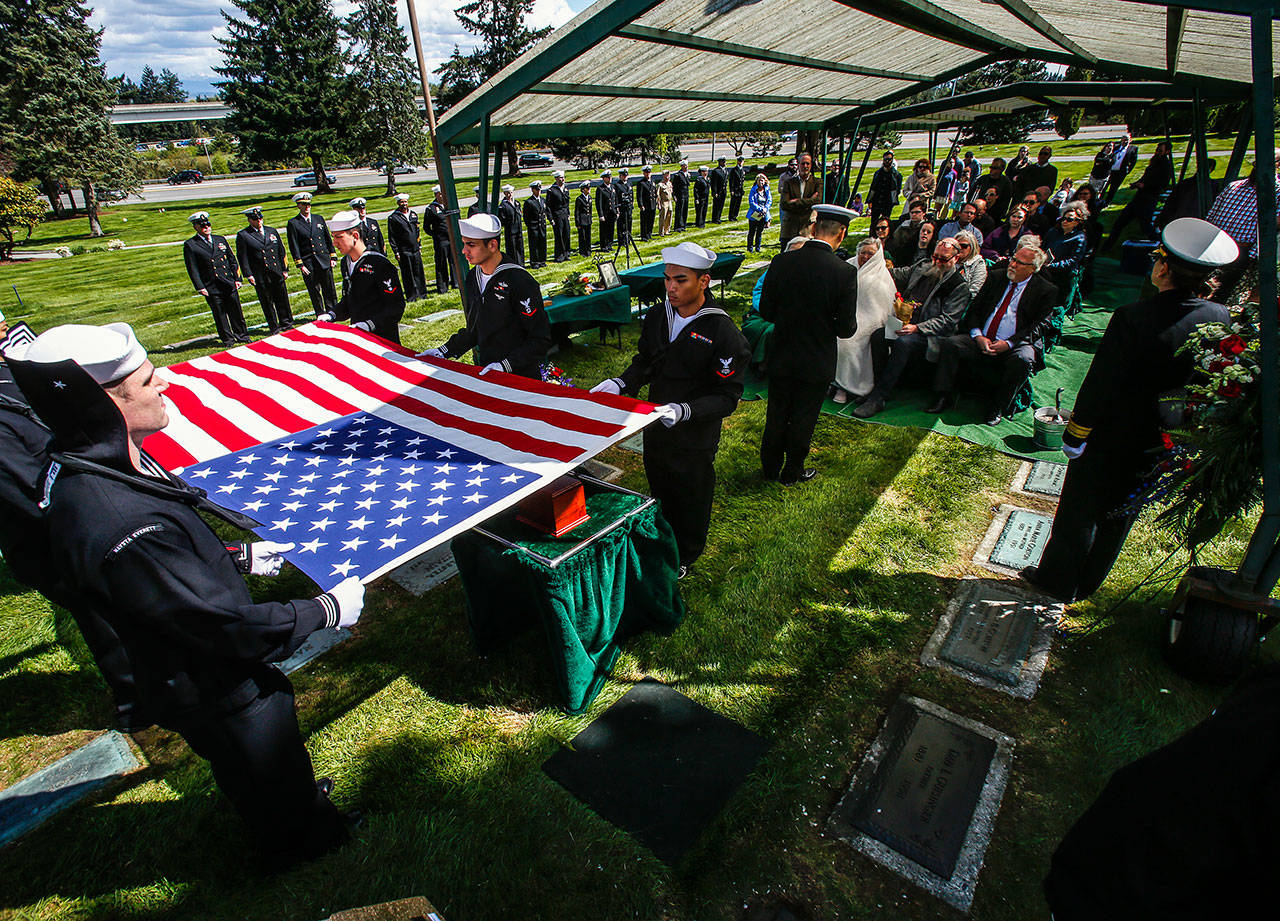Sailors hold an American flag over the urn bearing Daniel Guisinger's ashes before the Everett sailor is buried at Cypress Lawn Memorial Park on April 27. He was killed at Pearl Harbor, and his remains were recently identified using DNA. (Dan Bates / The Herald)