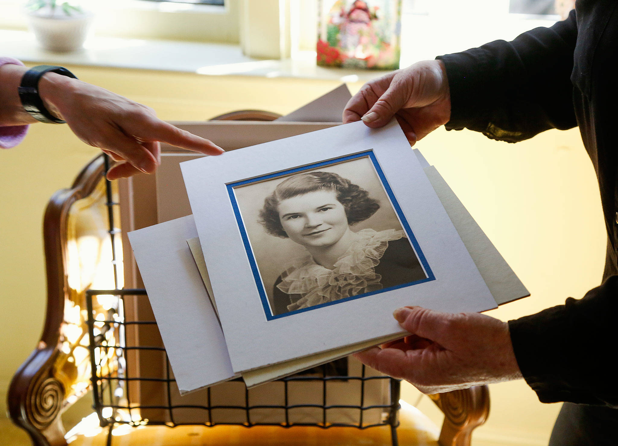 "In the north Everett home where she and her sister Margaret ""Mugsy"" Duryee grew up, Maureen Duryee sorts through photographs of their mother Mary Duryee. This portrait was Mary's Everett High School 1935 graduation portrait. She died April 22 at age 100. (Dan Bates / The Herald)"