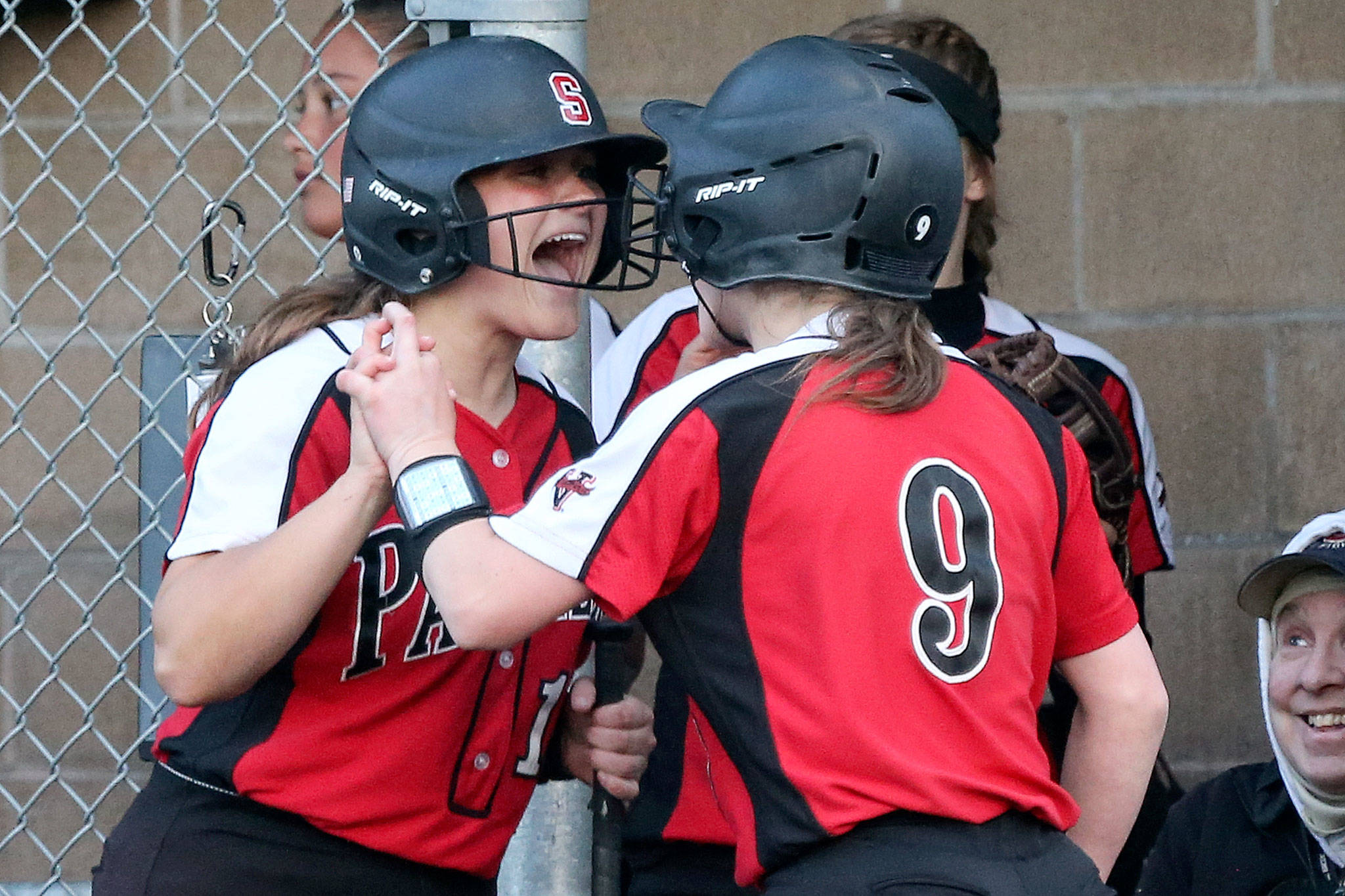 Snohomish's Anna Robinson (left) celebrates with Janell Williams after Williams scores a run Wednesday night at Lincoln Field in Everett on May 1, 2019. (Kevin Clark / The Herald)