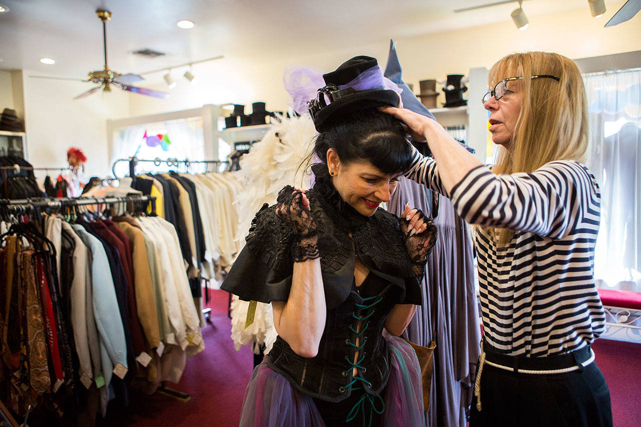 Owner Cyd Hand helps customer Barbara Kiesling try on a hat at Vintage Costumers in Everett. (Olivia Vanni / The Herald)