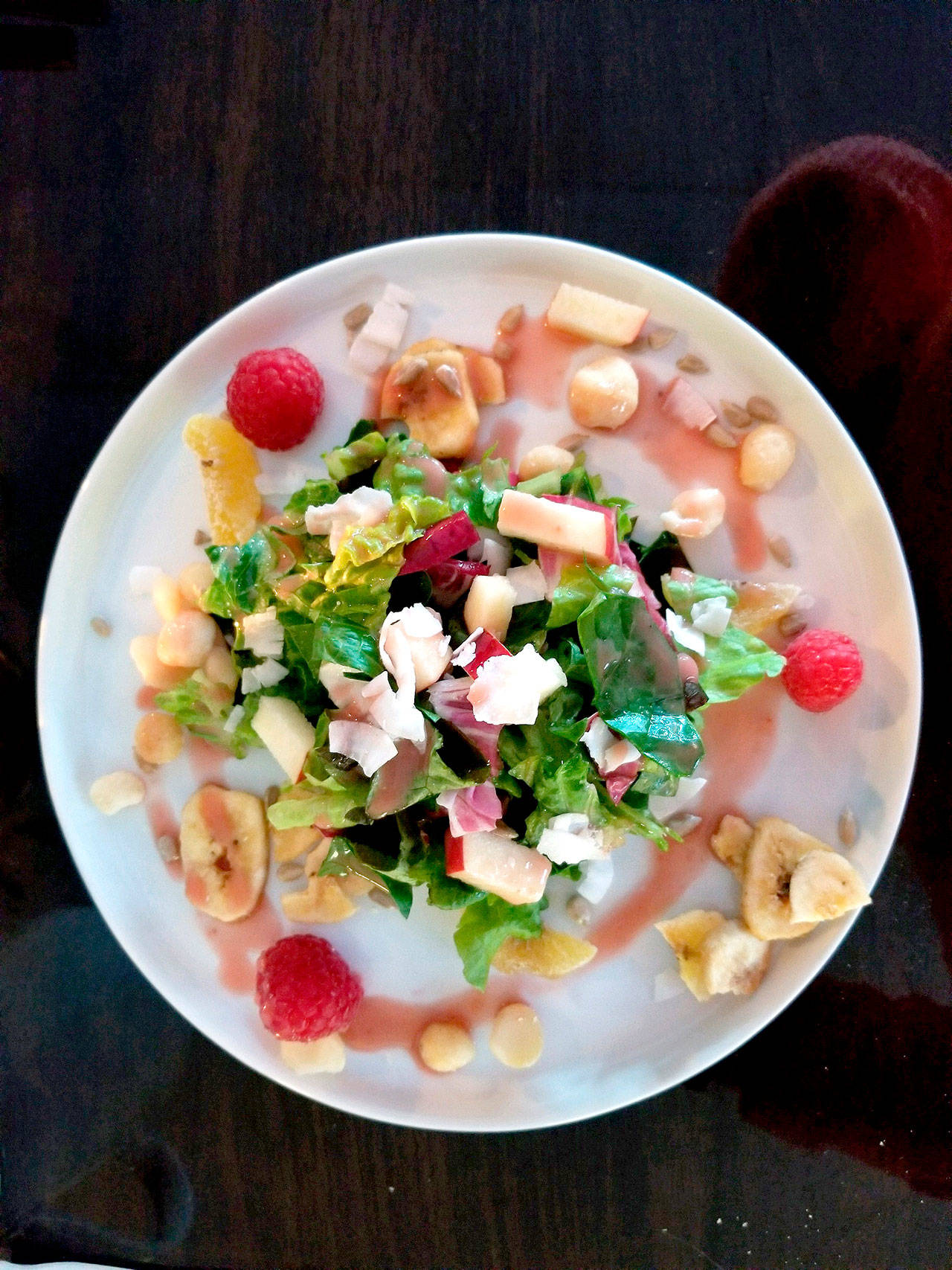 """The """"Dreaming of Vacation"""" salad at Crow Island Farms is a plate of mixed greens topped with a summery assortment of banana chips, coconut shavings, dried kiwi, raspberries, apples, macadamia nuts and sunflower seeds, and dressed with a strawberry vinaigrette. (Pam Bruestle)"""