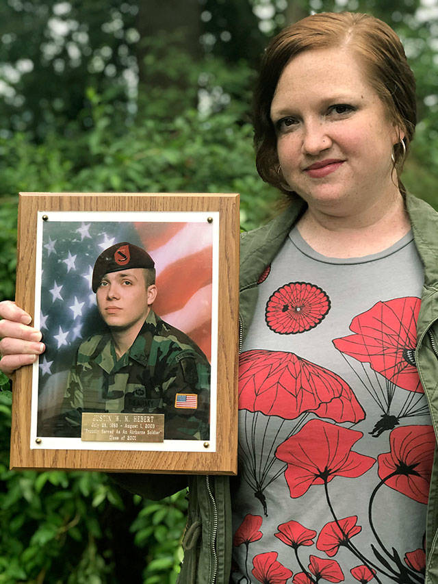Jessica Hebert holds a photo of her brother, Army Spc. Justin Hebert, who was killed in combat in Iraq at age 20 in 2003. Hebert, of Everett, spoke at the luncheon for volunteers at a Habitat for Humanity Veterans Build event in Gold Bar. (Andrea Brown / The Herald)