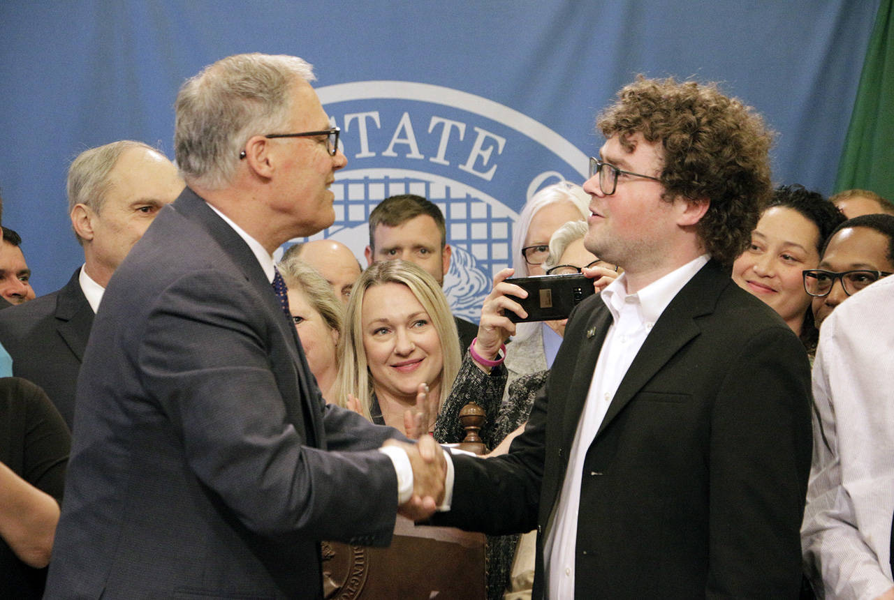 "Gov. Jay Inslee shakes hands with Joshua Stuller after deeming him ""Washingtonian of the Day"" following the signing of a bill that seeks to speed up competency evaluations for defendants at jails, on Thursday in Olympia. Stuller, who advocated for the legislation, was released from Eastern State Hospital last year. (AP Photo/Rachel La Corte)"