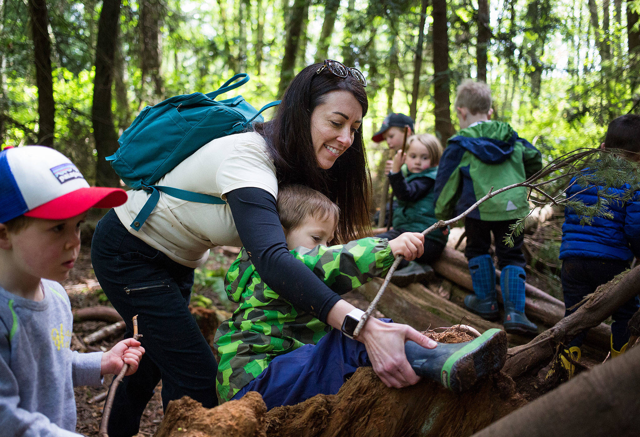 """Kristin Hammer, owner of Nature Together, helps a stuck Lincoln Mays, 3, climb out of a tree stump in an area called the kids call the """"pirate ship"""" in Japanese Gulch Park on May 1 in Mukilteo. The preschool specializes in day classes with an environment theme. (Andy Bronson / The Herald)"""