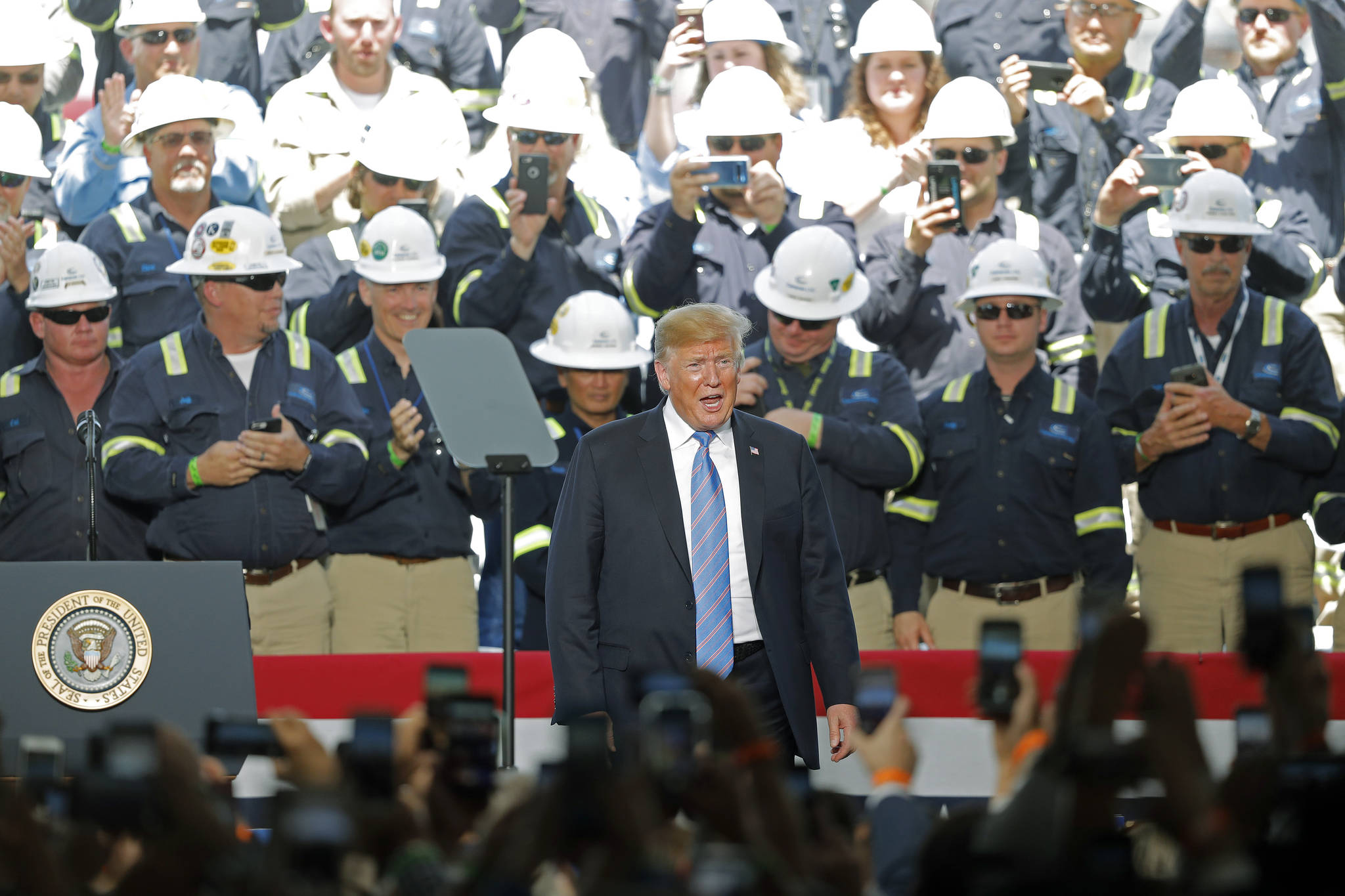 Gerald Herbert / Associated Press                                 Workers applaud President Donald Trump as he arrives Tuesday to speak at the Cameron LNG Export Terminal in Hackberry, Louisiana.