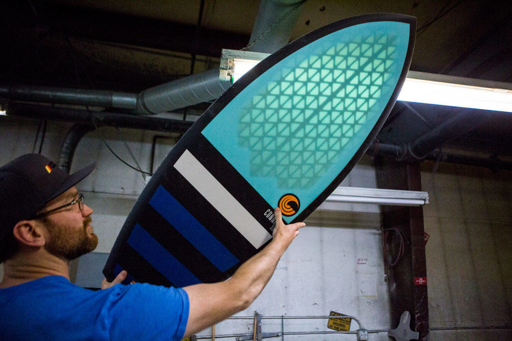 Connelly Skis marketing manager Collin Spradlin reveals the structure that helps make a board lighter. (Olivia Vanni / The Herald)