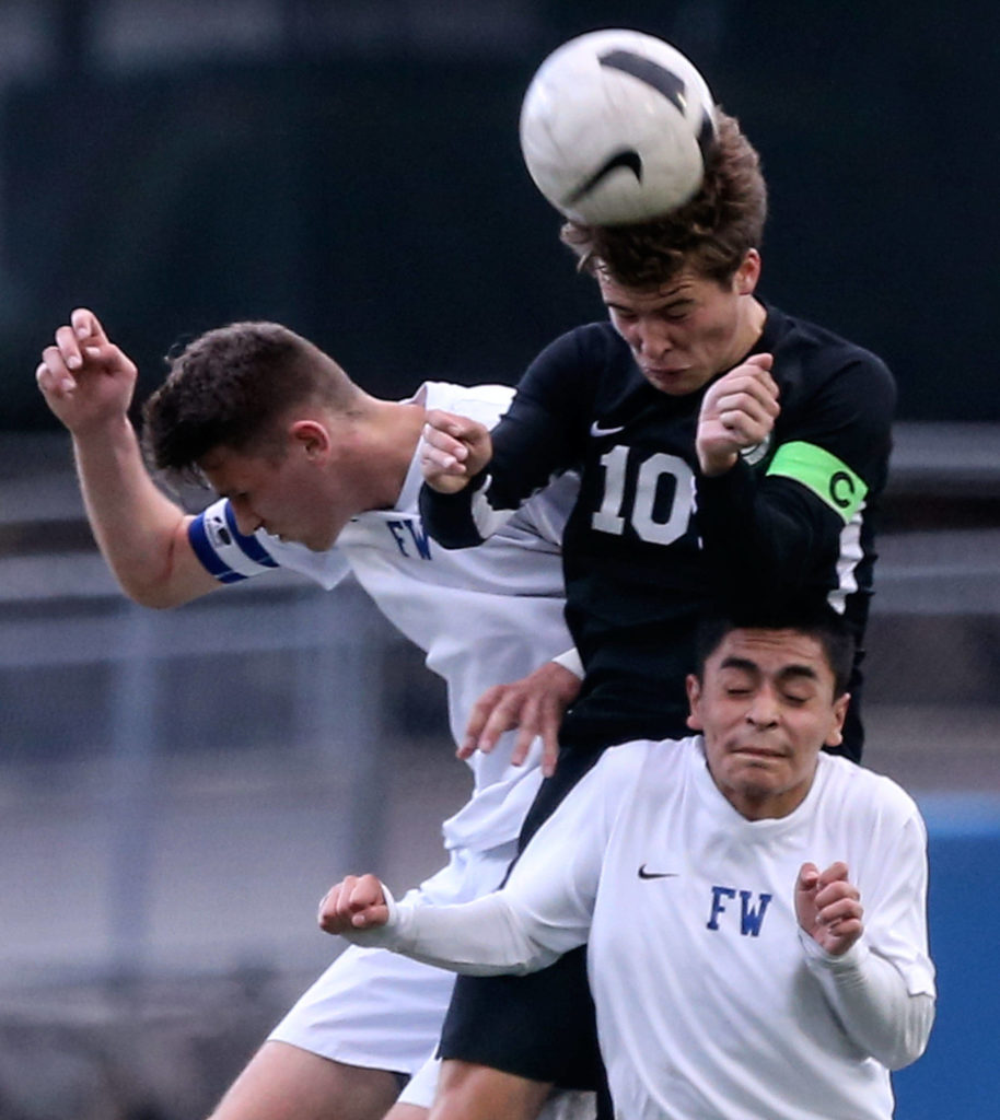 Jackson's Jacob Williams out-jumps Federal Way's Zane Baumgardt (left) and Carlos Quijada for a header during a 4A state soccer match on May 17, 2019, at Everett Memorial Stadium. The Timberwolves won 2-1. (Kevin Clark / The Herald)