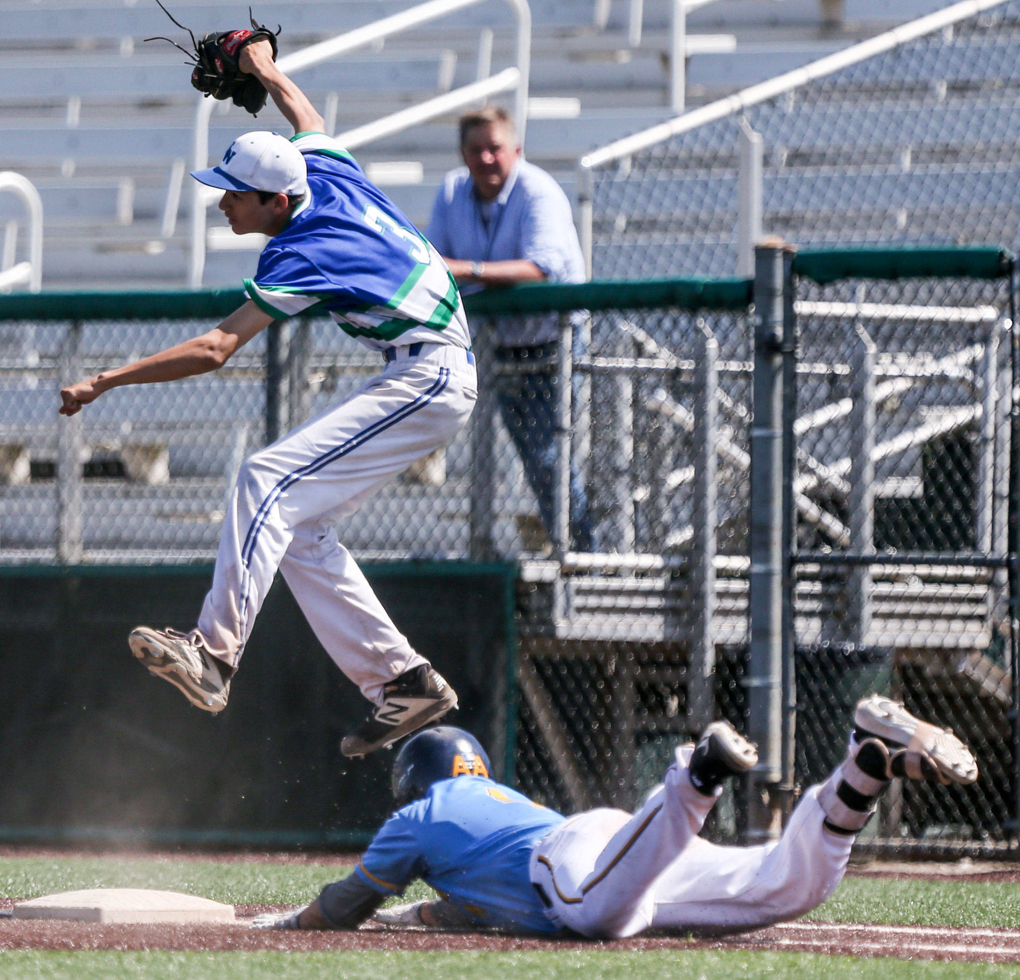 Everett's Tyler Bates slides into first under Shorewood's Kenji Miller during the 3A District title game at Funko Field in Everett on May 11. The Seagulls won 6-0. (Kevin Clark / The Herald)
