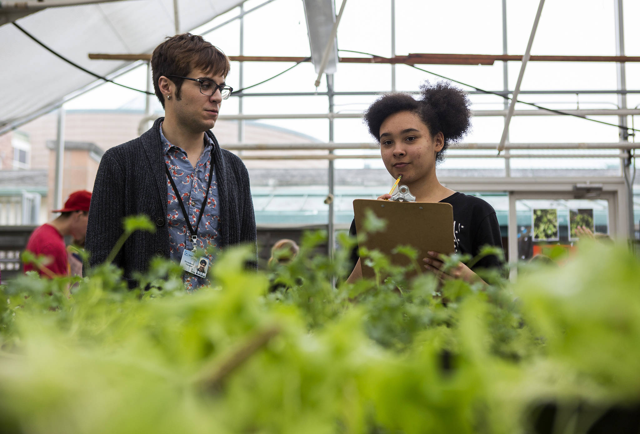 Greg McMichael (left) helps Emily Harris (right) with a plant order during the Functional Life Academics plant sale at Kamiak High School on May 14 in Mukilteo. (Olivia Vanni / The Herald)