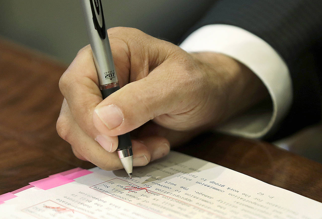 Washington Gov. Jay Inslee uses a red pen to veto sections of the state operating budget Tuesday at the Capitol in Olympia. (AP Photo/Ted S. Warren)