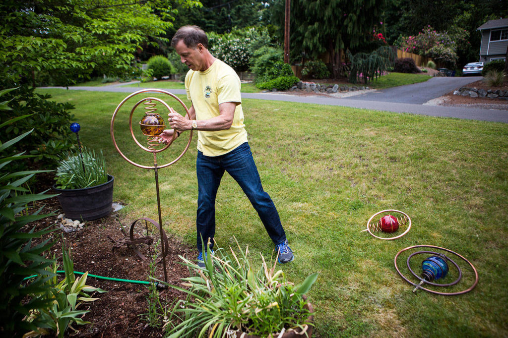 Steve Hopkins puts together a spinning sprinkler in the front yard of his home. (Olivia Vanni / The Herald)