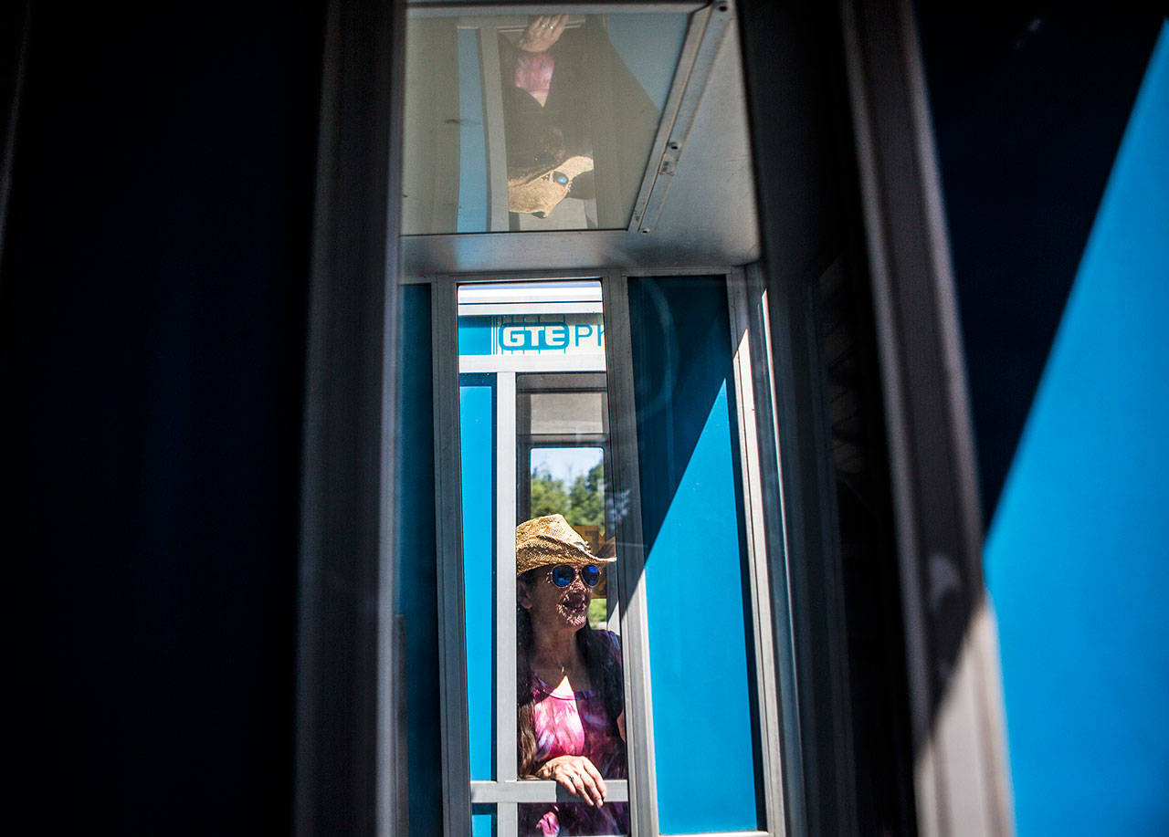 Store owner Cynthia Marie in one of her phone booths for sale. (Olivia Vanni / The Herald)