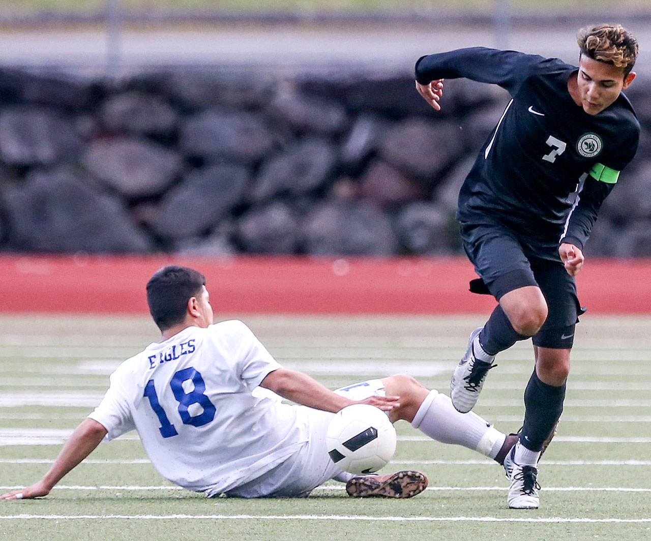 Jackson's Kevin Giessler (right) avoids a tackle attempt by Federal Way's David Sanchez-Benetiz during a game on May 17, 2019, at Everett Memorial Stadium. (Kevin Clark / The Herald)