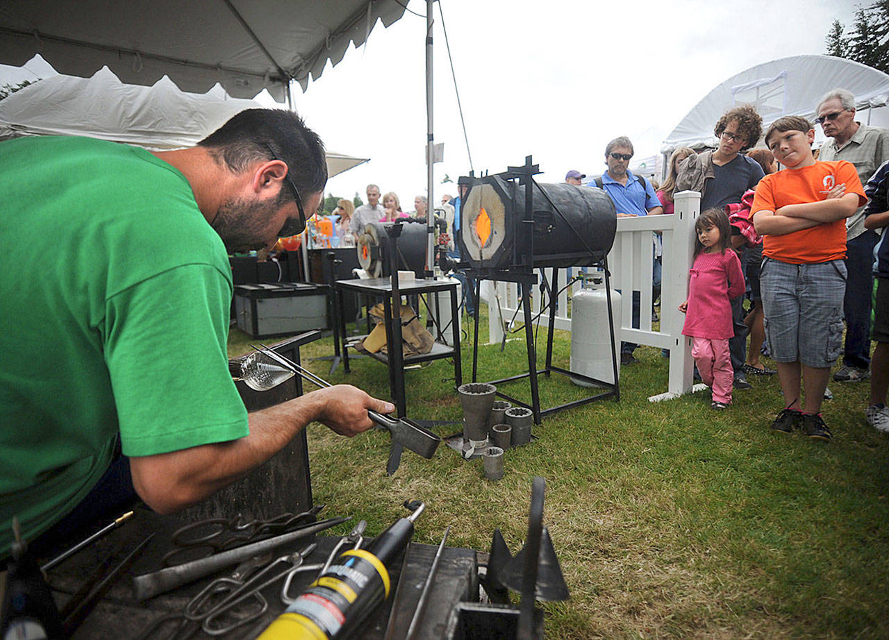 Glass blowing artist Chris Schuelke works on making a glass goblet during a demonstration at the Edmonds Arts Festival in 2015. (Herald file)