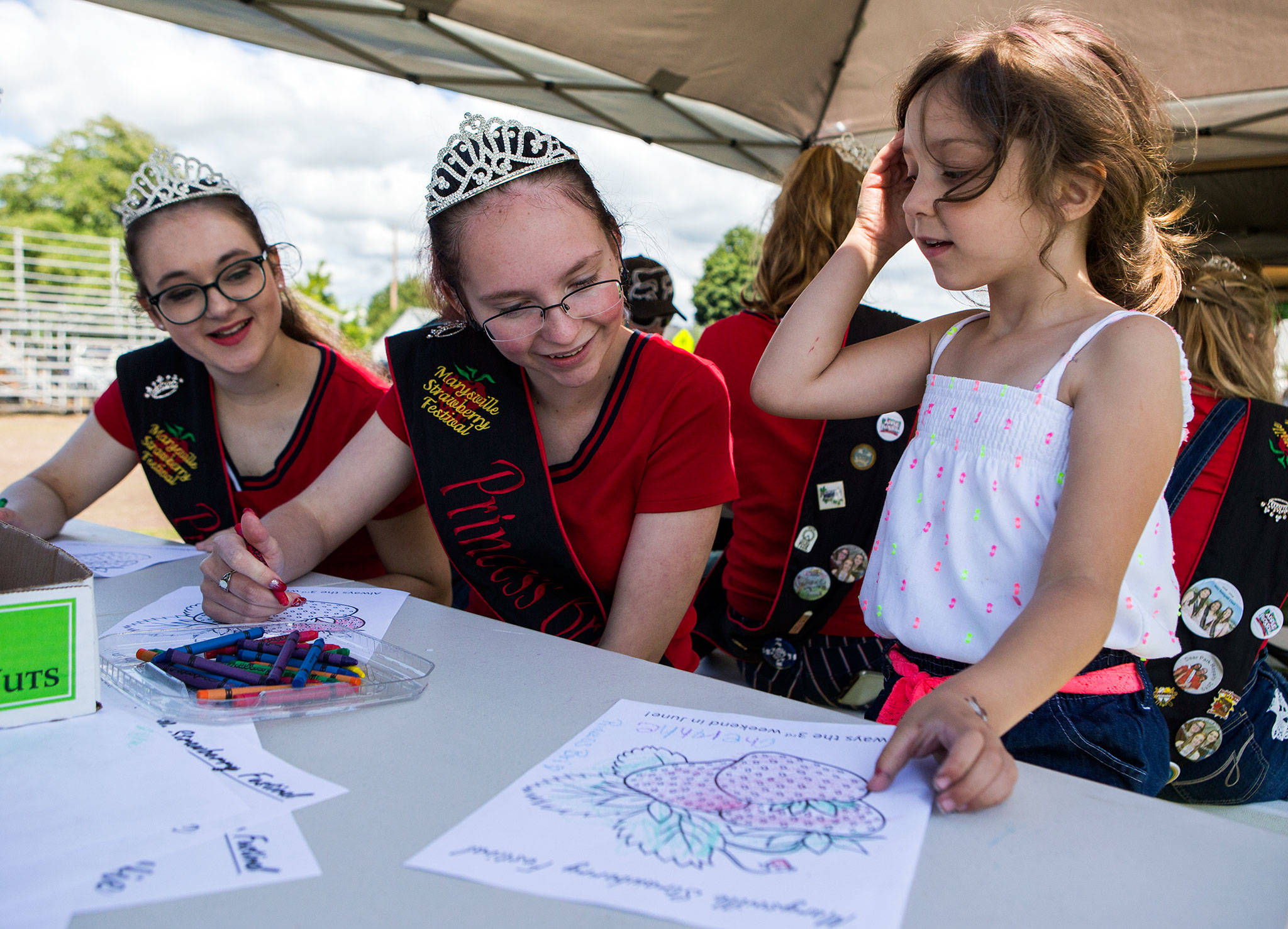 Cheyanne Schwarz, 5, far right, shows Marysville Strawberry Festival princesses Jael Hudson, left, and Bri Olson, center, her finished strawberry coloring sheet during Kids Day at the Strawberry Festival on June 8 in Marysville. (Olivia Vanni / The Herald)