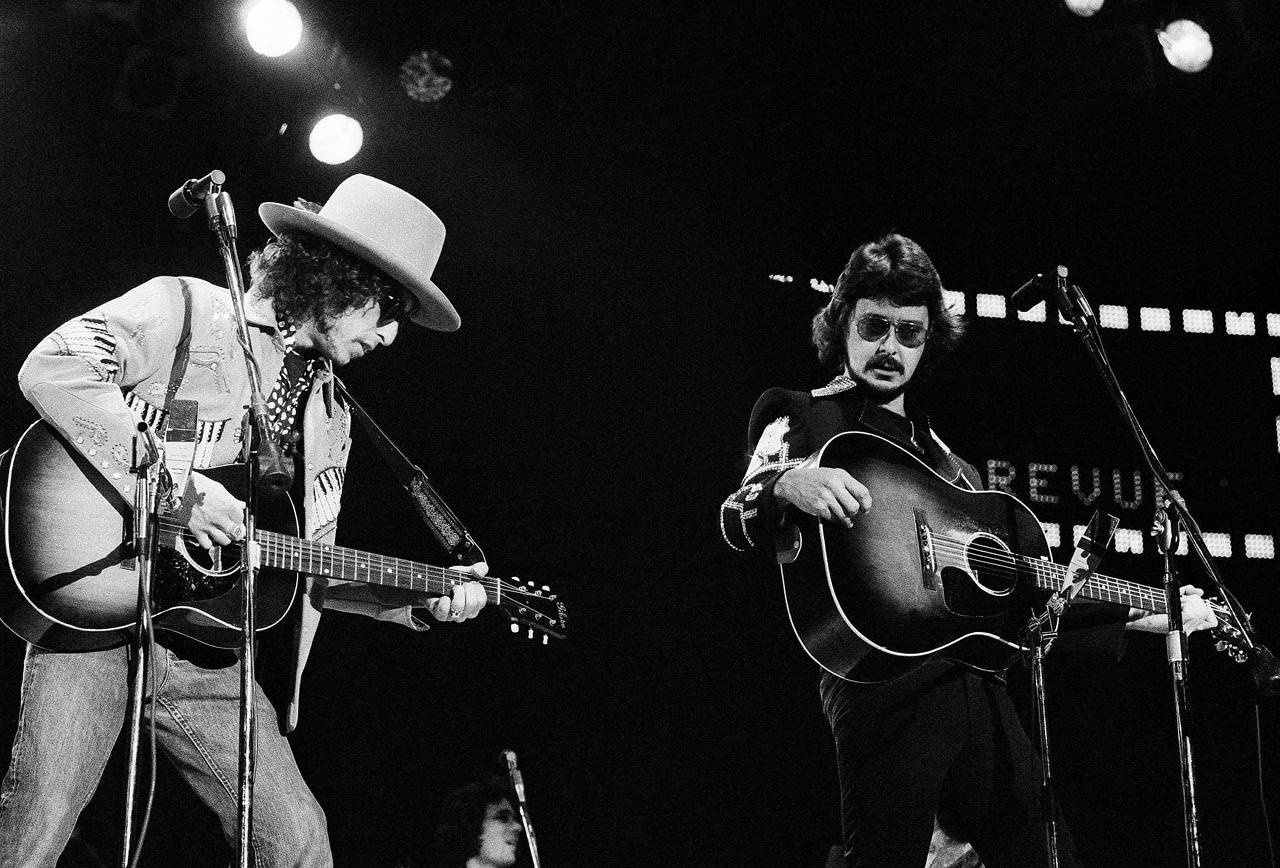 Bob Dylan (left) and the Rolling Thunder Revue perform in January 1976. Musician Bob Neuwirth is at right. (Associated Press)
