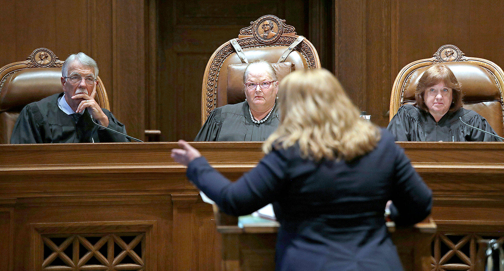 From left, Justice Charles W. Johnson, Chief Justice Mary E. Fairhurst and Justice Barbara A. Madsen listen to Michele Earl-Hubbard, the attorney for a media coalition, during a hearing before the Washington Supreme Court on Tuesday in Olympia. (AP Photo/Elaine Thompson)