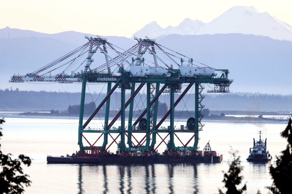 A pair of newly acquired port cranes make their way through Puget Sound off Mukilteo Tuesday after a 1,400-mile ocean journey from Los Angeles. (Kevin Clark / The Herald)