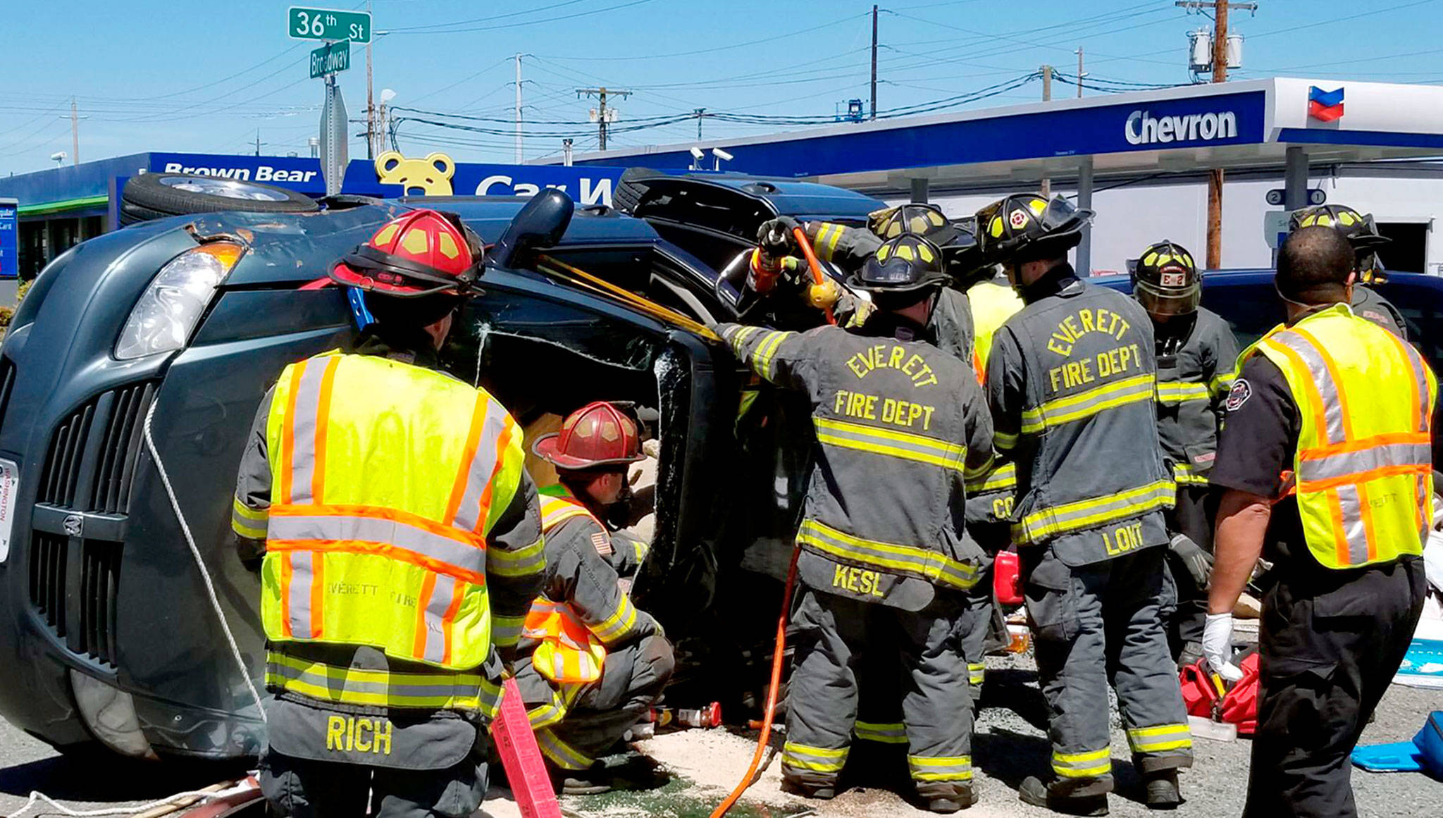 Firefighters work to extricate the driver of a car that rolled over Tuesday afternoon at the intersection of Broadway and 36th Street in Everett. (Everett Fire Department)