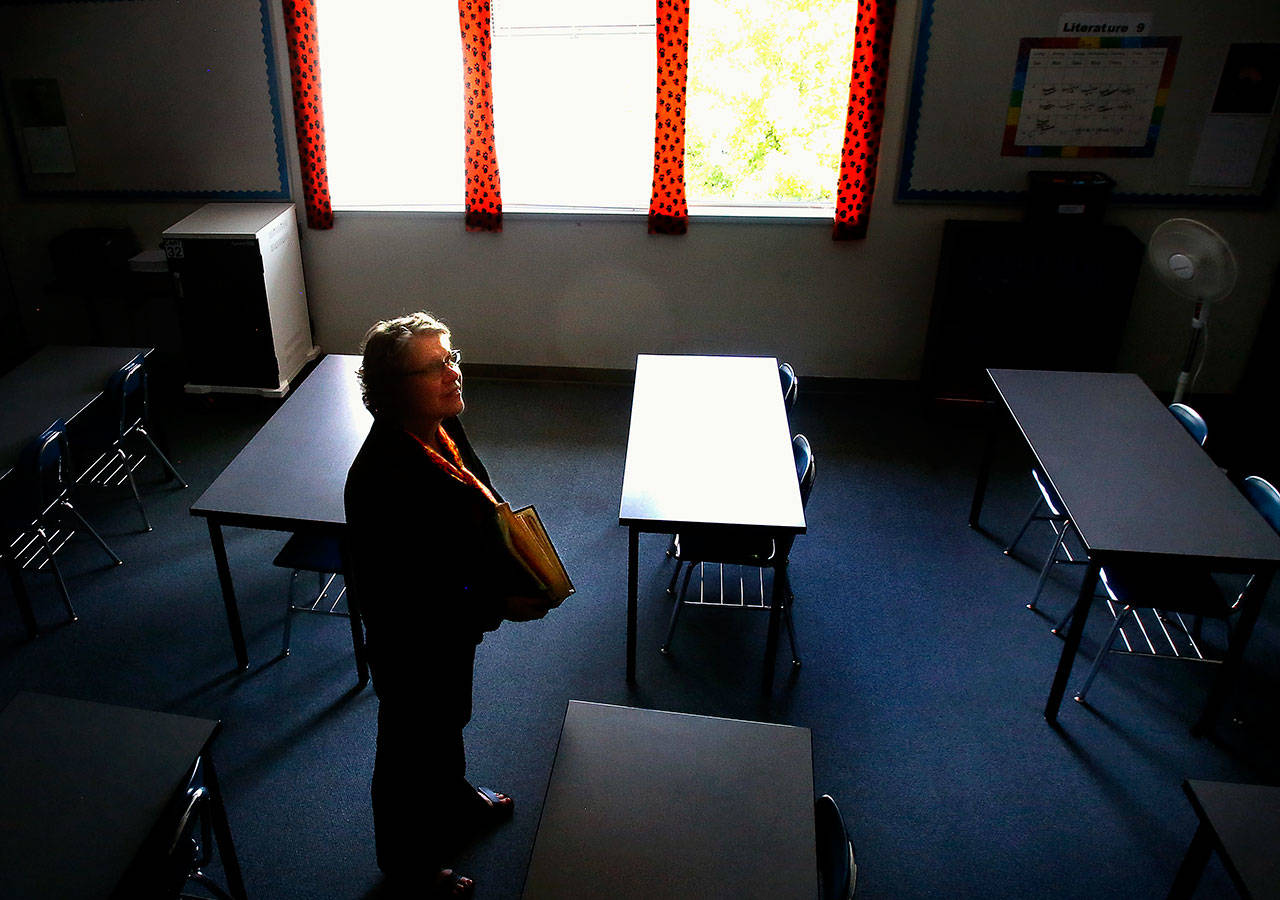 Carrying a scrapbook filled with photos and memories of former students, special education teacher Susan Dow is ready to leave her Monroe High classroom for the last time. (Dan Bates / The Herald)