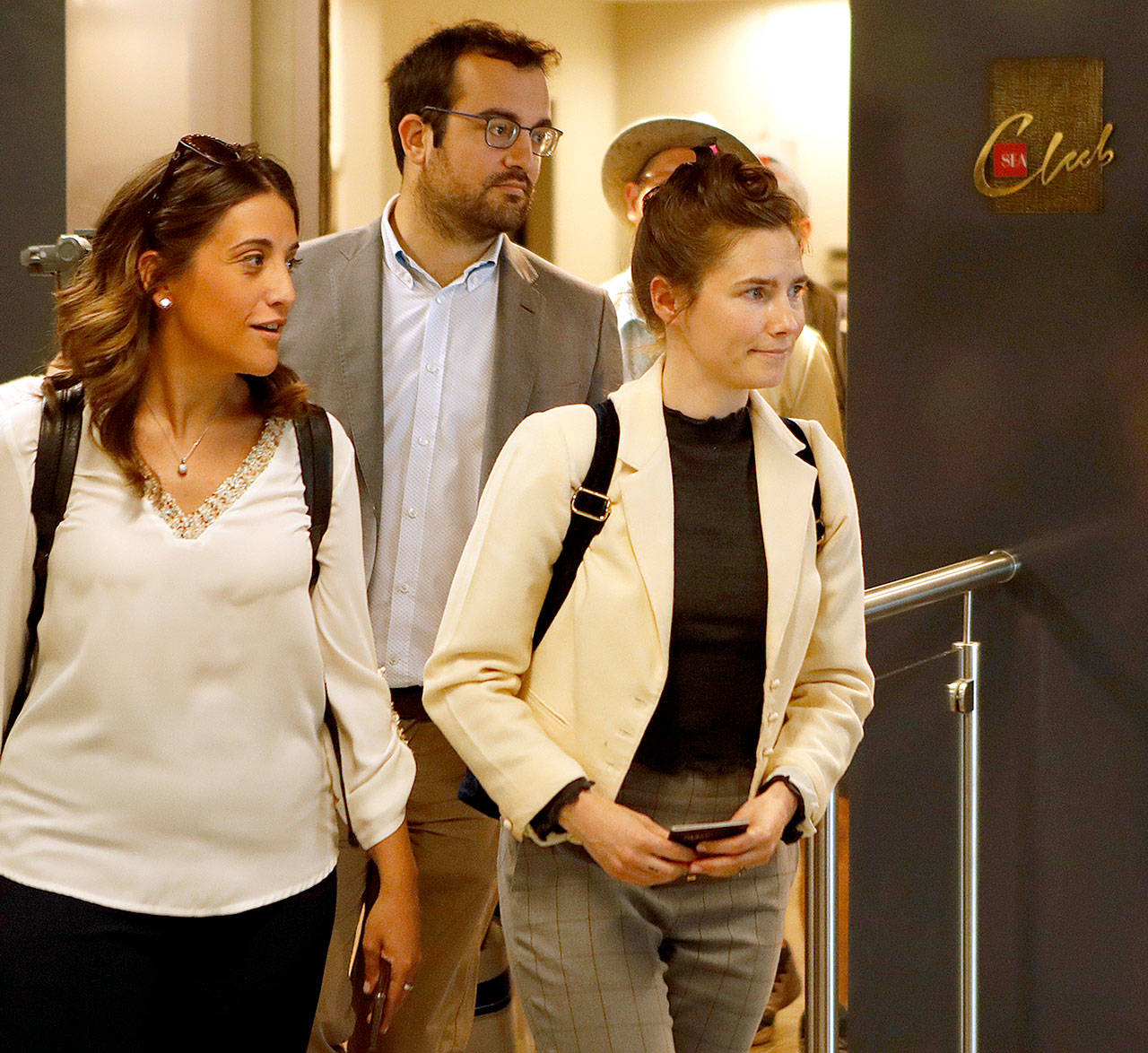 Amanda Knox (right) exits the airport from a side entrance upon her arrival in Milan, Italy, on Thursday. She has returned to Italy for the first time since she was convicted and imprisoned, but ultimately acquitted, for the murder and sexual assault of her British roommate. Knox will attend a conference rganized by the Italy Innocence Project, which seeks to help people who have been convicted for crimes they did not commit. (AP Photo/Antonio Calanni)