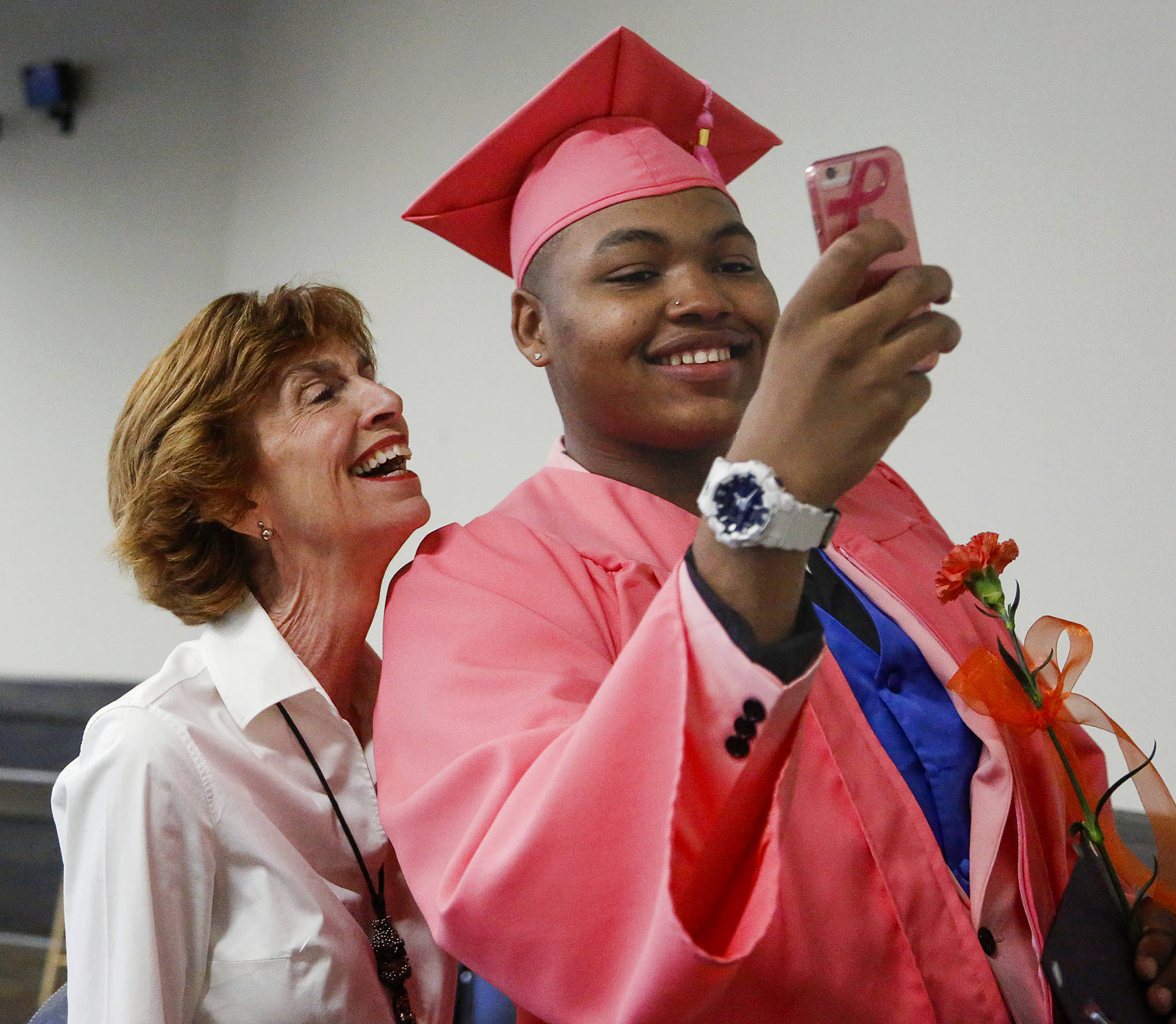 """Terrence Barton, 20, takes a selfie with his mentor Laura Wilson at the <a href=""""https://www.heraldnet.com/news/you-did-it-worksource-grads-encouraged-to-take-next-step/"""" target=""""_blank"""">WorkSource Youth Center graduation ceremony</a> June 10. (Dan Bates / The Herald)"""