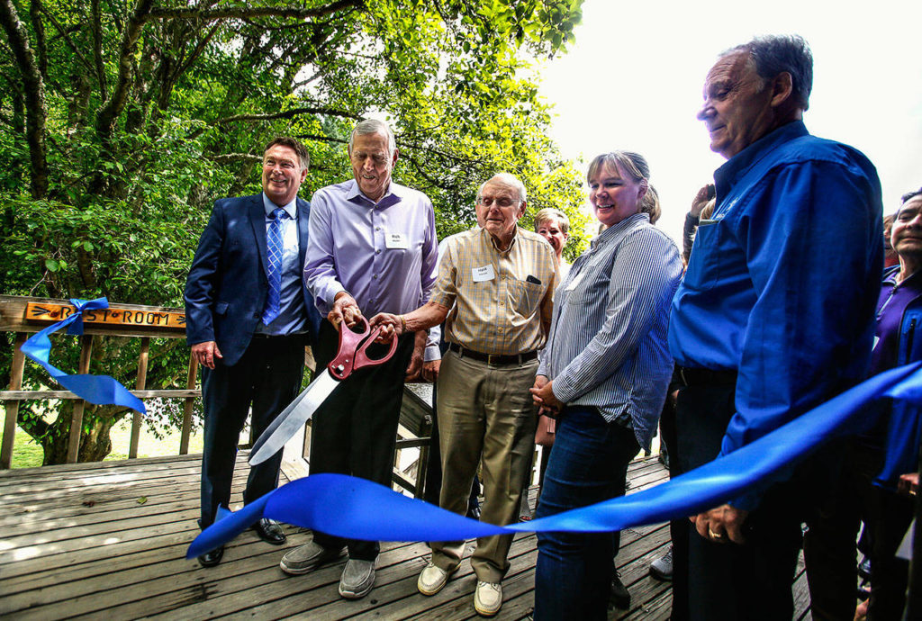 From left, Jim Stephanson, Rich Boyden, Hank Robinett, Krissy Davis and Dave Surface perform a traditional ribbon cutting, with Boyden and Robinett manning the scissors on the deck of Camp Killoqua's lodge Thursday. Earlier, they thanked donors who gave nearly $2.2 million that will help boost the number of kids served from 8,000 to 12,000. (Dan Bates / The Herald)