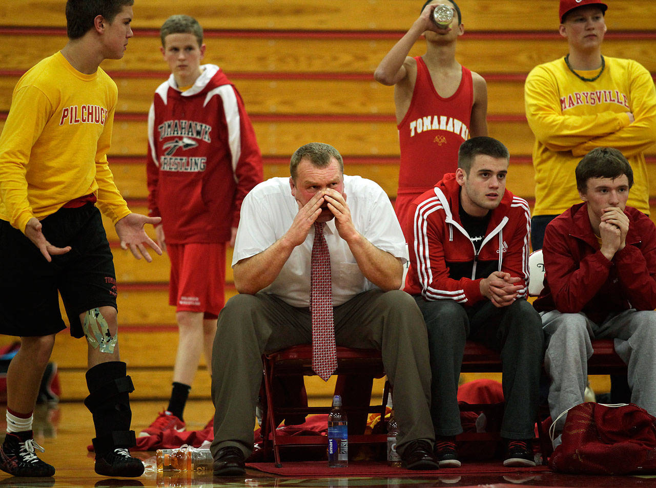 Marysville-Pilchuck head wrestling coach Craig Iversen, center, cheers on his team Dec. 12, 2012 during a nonconference meet against Arlington High School, then coached by his father, Rick Iversen. (Annie Mulligan / Herald file)