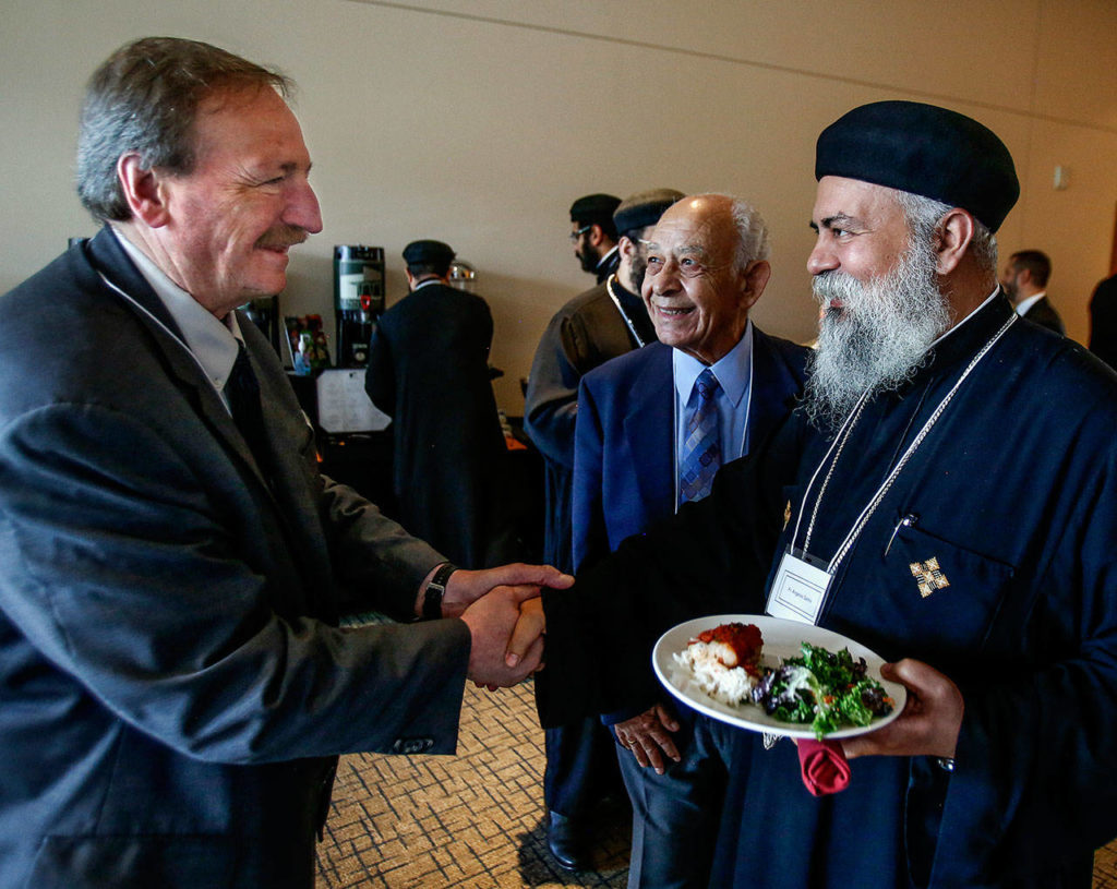Dave Somers shakes hands with Fr. Angelos Sarkis Friday at the Lynnwood Convention Center during a break from a meeting with members of the Muslim Egyptian and Coptic Christian Egyptian communities.