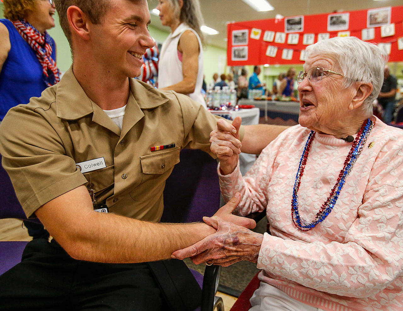 To the delight of her water aerobics pals, the 100-year-old birthday girl really enjoys the young sailors, including Corpsman Recruit Kristian Colwell from Naval Station Everett, attending the party. (Dan Bates / The Herald)
