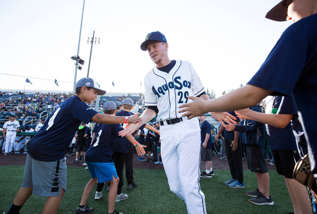 The AquaSox's Tim Elliott get high fives as he is introduced before Everett's home opener against the Volcanoes on June 21, 2019, at Funko Field at Everett Memorial Stadium. (Andy Bronson / The Herald)